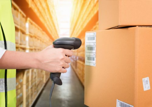 Woman scanning barcode from a label in modern warehouse